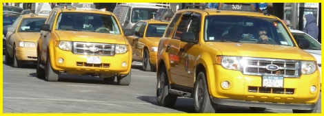 Taxi cabs traveling down New York's Fifth Avenue.