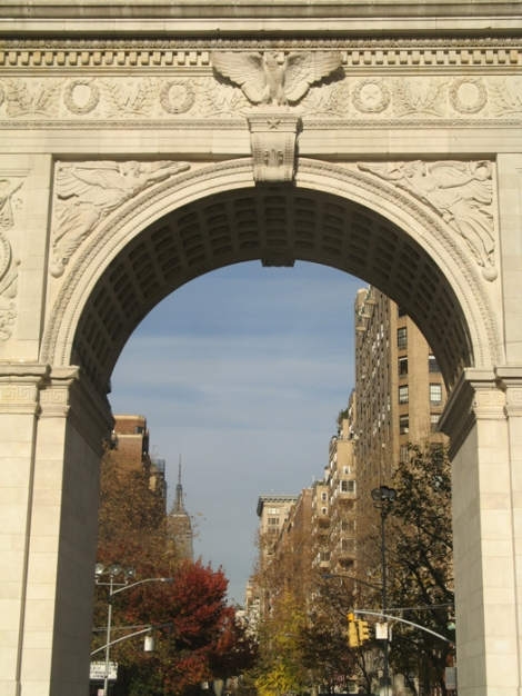 The Empire State Building can be seen through the arch in the distance, on the left.