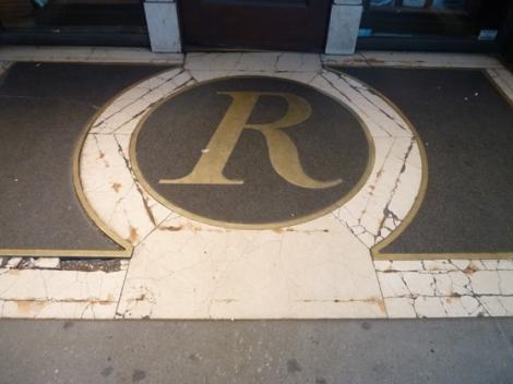Rizzoli, marble, sidewalk, brass, logo